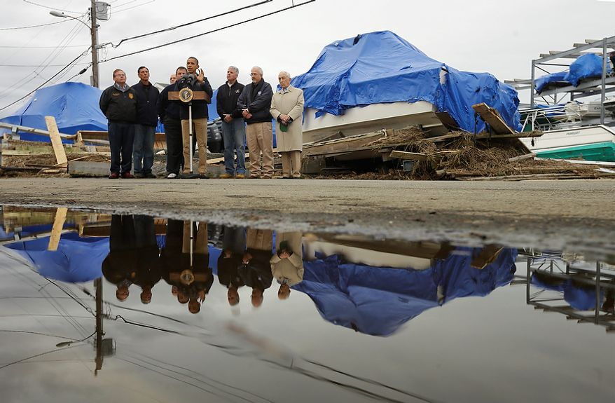 President Obama (center), with New Jersey Gov. Chris Christie, Federal Emergency Management Agency Administrator Craig Fugate, and other local and federal officials, speaks about the superstorm Sandy relief efforts while standing in front of North Point Marina on Wednesday, Oct. 31, 2012, in Brigantine, N.J. (AP Photo/Pablo Martinez Monsivais)