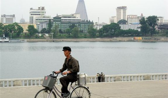 A cyclist rides along the banks of the River Taedong in Pyongyang, North Korea, on Friday, June 1, 2007. The pyramid in the background is the Ryogyong Hotel, on which construction began in 1987 but was abandoned unfinished in 1991. (AP Photo/Michael Fischer)