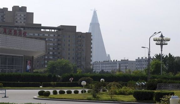 In this photo from Wednesday, Sept. 16, 2009, the 105-story, pyramid-shaped Ryugyong Hotel, still under construction, is seen in the distance from a street in Pyongyang, North Korea. After years of delay, construction has resumed on the hotel with some windowpanes installed on the facade. (AP Photo/Jean H. Lee)