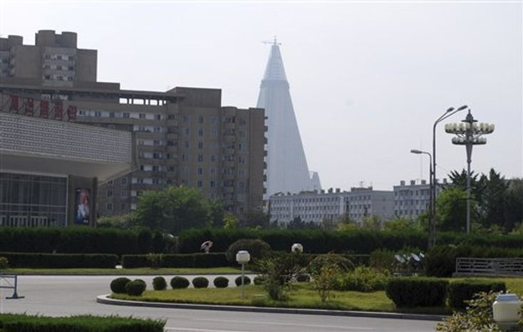 In this photo from Wednesday, Sept. 16, 2009, the 105-story, pyramid-shaped Ryugyong Hotel, still under construction, is seen in the distance from a street in Pyongyang, North Korea. After years o