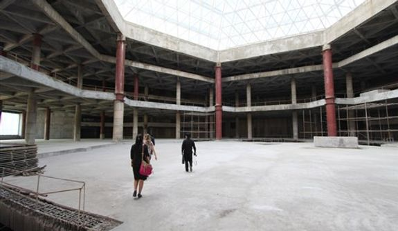 In this Sept. 23, 2012, photo released by Koryo Group, visitors tour the top floor of the 105-story Ryugyong Hotel in Pyongyang, North Korea. After years of standing unfinished, construction on the exterior of the massive hotel resumed three years ago, but the hotel has not yet opened to the public. This photo, taken by the Beijing-based Koryo Tours, shows that the interior remains unfinished. (AP Photo/Koryo Group)