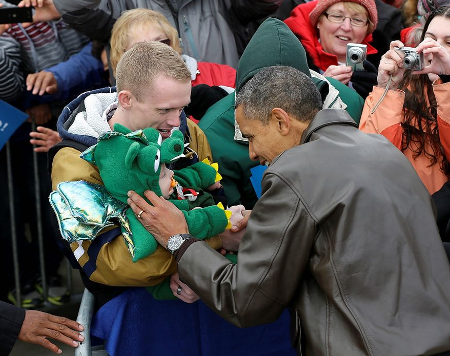 President Obama stops to greet a small child in a dragon costume during a campaign event at Austin Straubel International Airport in Green Bay, Wis., on Thursday, Nov. 1, 2012. Mr. Obama resumed his presidential campaign with travel to the key battleground states of Wisconsin, Colorado, Nevada and Ohio today. (AP Photo/Pablo Martinez Monsivais)