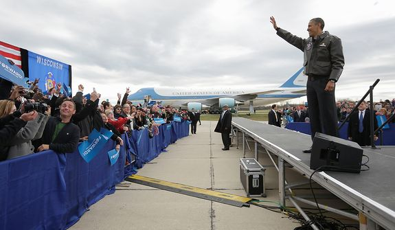 President Obama waves to supporters during a campaign event at Austin Straubel International Airport in Green Bay, Wis., on Thursday, Nov. 1, 2012. Mr. Obama resumed his presidential campaign with travel to the key battleground states of Wisconsin, Colorado, Nevada and Ohio today. (AP Photo/Pablo Martinez Monsivais)
