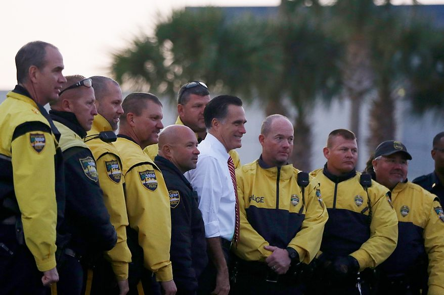 Republican presidential candidate, former Massachusetts Gov. Mitt Romney poses for a photo with law enforcement members which escorted his motorcade before boarding his  campaign plane in Jacksonville, Fla., Thursday, Nov. 1, 2012, enroute to campaign stops in Virginia. (AP Photo/Charles Dharapak)