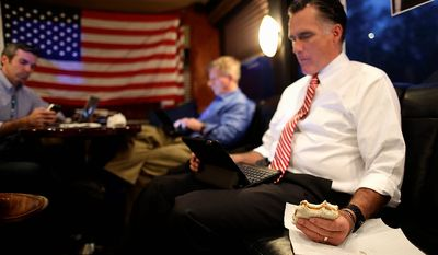 Republican presidential candidate and former Massachusetts Gov. Mitt Romney holds a peanut butter and honey sandwich he made for himself as he looks over his iPad while seated in the back of his campaign bus with chief strategist Stuart Stevens, center, and senior adviser Kevin Madden as they leave a campaign event at Meadow Event Park, in Dowell, Va., for another rally in Virginia Beach, Va., Thursday, Nov. 1, 2012. (AP Photo/Charles Dharapak)