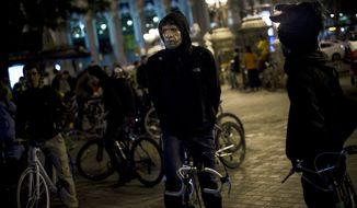 """A man wearing a mask waits to take part in a flash mob named """"Halloween bike ride"""" before touring around the city in Madrid, Tuesday, Oct. 31, 2012. (AP Photo/Daniel Ochoa de Olza)"""