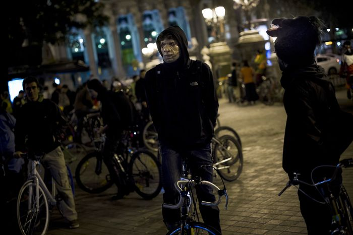 "A man wearing a mask waits to take part in a flash mob named ""Halloween bike ride"" before touring around the city in Madrid, Tuesday, Oct. 31, 2012. (AP Photo/Daniel Ochoa de Olza)"