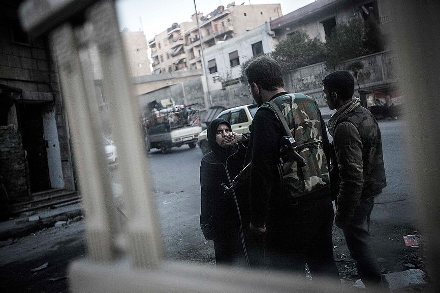 In this Tuesday, Oct. 30, 2012 photo, a Syrian woman is stopped and questioned by rebels at a checkpoint in the Bustan Al-Pasha neighborhood, the boundary of the controlled area by rebel fighters at the northeast limit of Sheikh Maaksoud in Aleppo, the Syria. (AP Photo/Narciso Contreras)