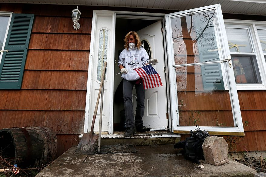 Kathleen Seemar removes a U.S. flag from her home, which was flooded during superstorm Sandy, as she started the cleanup process, Thursday, Nov. 1, 2012, in Brick, N.J. Three days after Sandy slammed the mid-Atlantic and the Northeast, New York and New Jersey struggled to get back on their feet, the U.S. death toll climbed to more than 80, and more than 4.6 million homes and businesses were still without power. (AP Photo/Julio Cortez)