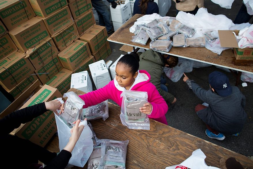 A young woman helps bag Meals-Ready-to-Eat (MREs) for distribution to the residents of the Lower East Side who remain without power due to Superstorm Sandy, Friday, Nov. 2, 2012, in New York. In Manhattan, where 226,000 buildings, homes and business remain without power, Consolidated Edison says they should have service restored by Saturday. (AP Photo/ John Minchillo)