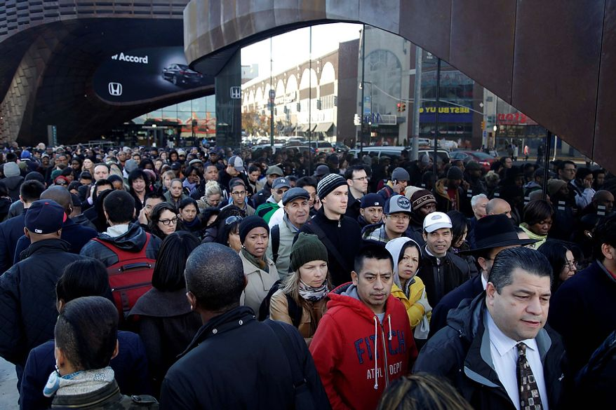 Commuters wait in a line to board busses into Manhattan in front of the Barclays Center in Brooklyn, New York, Thursday, Nov. 1, 2012.  The line stretched twice around the arena and commuters reported wait times of one to three hours to get on a bus. (AP Photo/Seth Wenig)