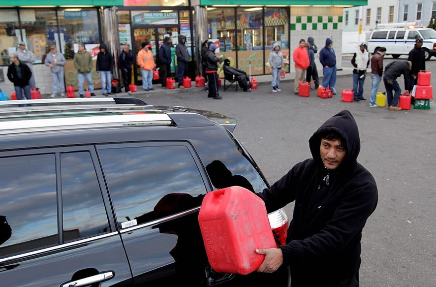 Mohammad Ullah fills up his gypsy cab from a gas container while others wait on a line in the Brooklyn borough of New York, Friday, Nov. 2, 2012.   In parts of New York and New Jersey, drivers face another day of lining up for hours at gas stations struggling to stay supplied.  Superstorm Sandy damaged ports that accept fuel tankers and flooded underground equipment that sends fuel through pipelines. Without power, fuel terminals can't pump gasoline onto tanker trucks, and gas stations can't pump fuel into customers' cars.  (AP Photo/Seth Wenig)