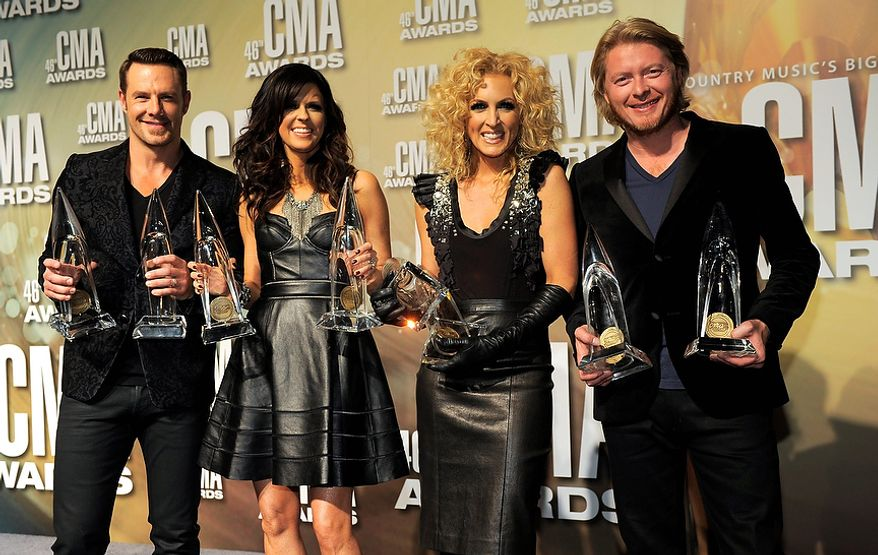 "Jimi Westbrook, from left, Karen Fairchild, Kimberly Schlapman and Phillip Sweet, of musical group Little Big Town, pose backstage with their awards for vocal group of the year and single of the year for ""Pontoon"" at the 46th Annual Country Music Awards at the Bridgestone Arena on Thursday, Nov. 1, 2012, in Nashville, Tenn. (Photo by Chris Pizzello/Invision/AP)"