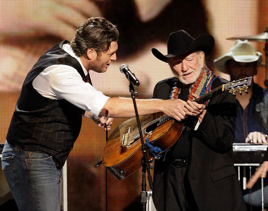 Blake Shelton, left, hands a guitar to Lifetime Achievement recipient Willie Nelson at the 46th Annual Country Music Awards at the Bridgestone Arena on Thursday, Nov. 1, 2012, in Nashville, Tenn. (Photo by Wade Payne/Invision/AP)