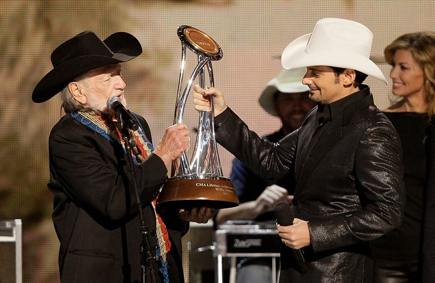 Brad Paisley, right, presents the Willie Nelson lifetime achievement award to Willie Nelson at the 46th Annual Country Music Awards at the Bridgestone Arena on Thursday, Nov. 1, 2012, in Nashville, Tenn. (Photo by Wade Payne/Invision/AP)