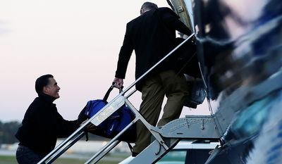 Republican presidential candidate and former Massachusetts Gov. Mitt Romney smiles as he jokingly holds onto the bag of campaign strategist Stuart Stevens as they board their plane in Norfolk, Va.,Friday, Nov. 2, 2012, as he travels to campaign events in Milwaukee, Wis. (AP Photo/Charles Dharapak)