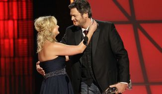 "Miranda Lambert, left, and Blake Shelton embrace onstage after winning the award for song of the year for ""Over You"" at the 46th Annual Country Music Awards at the Bridgestone Arena on Thursday, Nov. 1, 2012, in Nashville, Tenn. (Photo by Wade Payne/Invision/AP)"