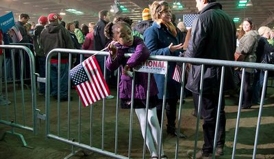 Constance Okonkwo, 5, holds an American flag while waiting for President Barack Obama to speak at a campaign event at the Franklin County Fairgrounds, Friday, Nov. 2, 2012, in Hilliard, Ohio, before heading to another campaign stop in in Springfield, Ohio. (AP Photo/Carolyn Kaster)
