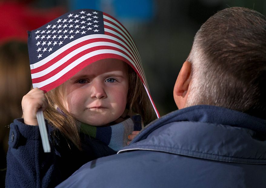 A little girl takes shelter under and American Flag before President Barack Obama arrives to speak at a campaign event at the Franklin County Fairgrounds, Friday, Nov. 2, 2012, in Hilliard, Ohio, before heading to another campaign stop in in Springfield, Ohio. (AP Photo/Carolyn Kaster)