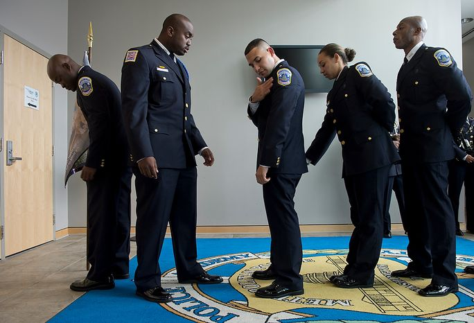 Metropolitan Police Department recruit class 2012-3 officers (from left) Deon George, Terrance Bradley, Guillermo Canales, Nicole Copeland and Terrence Craig make sure their uniforms are all situated before their graduation ceremony on Friday, Oct. 26, 2012 at the Metropolitan Police Academy in Southwest Washington, D.C. The class graduated 15 new police officers. (Barbara L. Salisbury/The Washington Times)