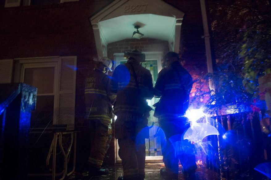 Fairfax County firefighters go door-to-door to check on residents on Arlington Terrace during a mandatory evacuation order in the Huntington neighborhood of Alexandria, Va., Monday, Oct. 29, 2012, while high winds and heavy rain from Hurricane Sandy pound the Atlantic coast. (Rod Lamkey Jr./The Washington Times)