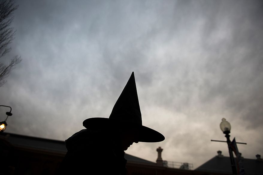 Michelle Carroll, of Washington, D.C., offers glow sticks and tooth brushes to kids, as residents arrive for Halloween festivities at Eastern Market in Washington, D.C., Wednesday, Oct. 31, 2012. (Rod Lamkey Jr./The Washington Times)