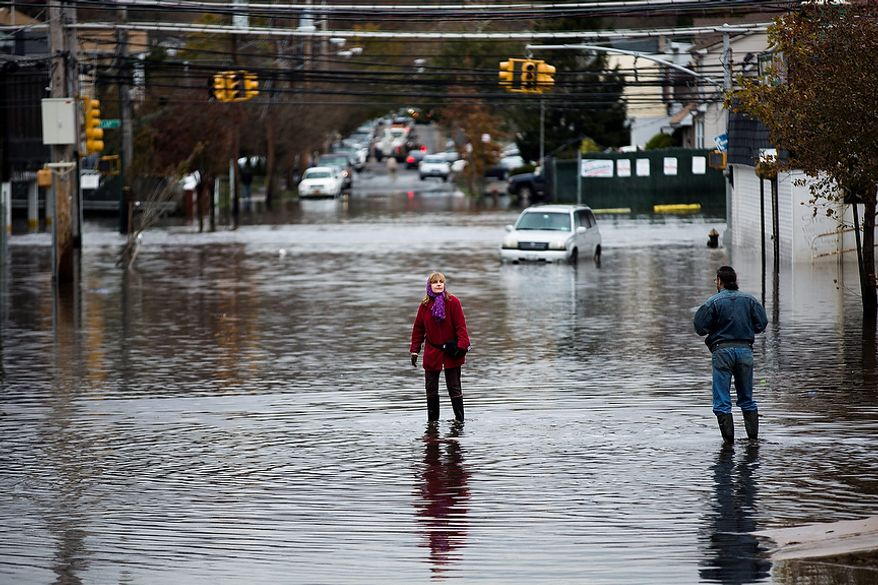 A woman stands in a street flooded by superstorm Sandy, Wednesday, Oct. 31, 2012, in the Staten Island borough of New York. Sandy, the storm that made landfall Monday, caused multiple fatalities, halted mass transit and cut power to more than 6 million homes and businesses. (AP Photo/John Minchillo)