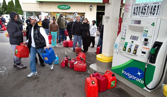 Customers form a queue to fill their gasoline canisters, Wednesday, Oct. 31, 2012, in the Staten Island borough of New York. Sandy, the storm that made landfall Monday, caused multiple fatalities, halted mass transit and cut power to more than 6 million homes and businesses.(AP Photo/ John Minchillo)
