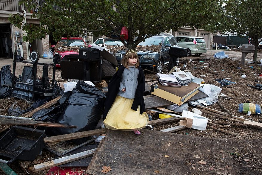 Lisa Kravchenko, of Staten Island, stands amongst flood debris in her princess Halloween costume, Wednesday, Oct. 31, 2012, in the Staten Island borough of New York. Sandy, the storm that made landfall Monday, caused multiple fatalities, halted mass transit and cut power to more than 6 million homes and businesses. (AP Photo/ John Minchillo)