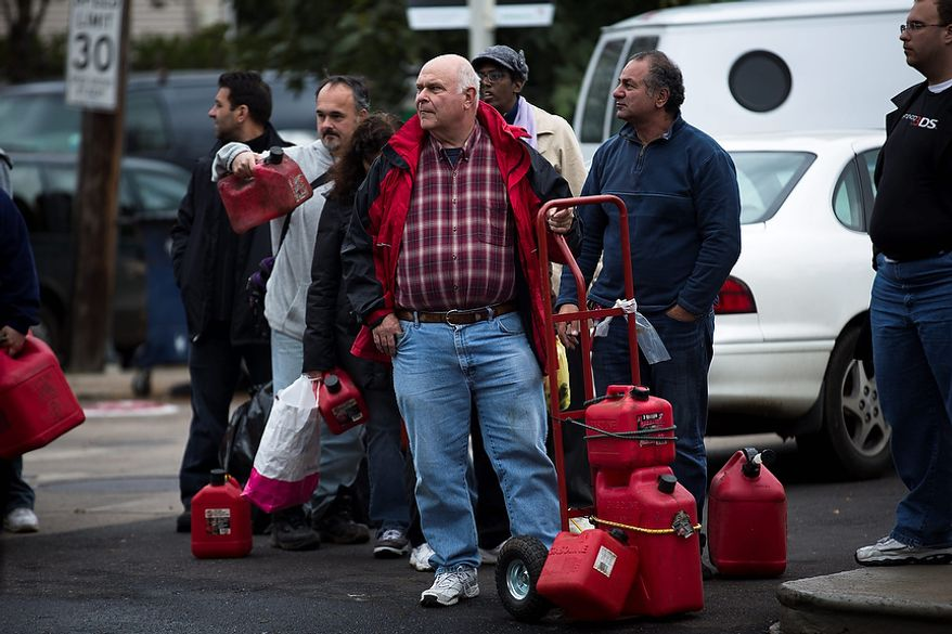 A man waits for gasoline, Wednesday, Oct. 31, 2012, in the Staten Island borough of New York. Sandy, the storm that made landfall Monday, caused multiple fatalities, halted mass transit and cut power to more than 6 million homes and businesses.(AP Photo/ John Minchillo)
