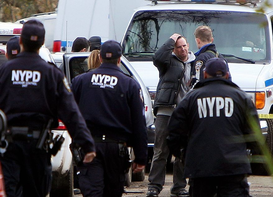 Damian Moore, reacts as he approaches the scene where at least one of his childrens' bodies were discovered in Staten Island, New York, Thursday, Nov. 1, 2012. Brandon Moore, 2, and Connor Moore, 4, were swiped into swirling waters as their mother tried to escape her SUV on Monday amid rushing waters that caused the vehicle to stall during Superstorm Sandy.  Police said the mother, Glenda Moore, was going to her sister's home in Brooklyn when she tried to flee the vehicle with the boys, only to have the force of the rising water and the relentless cadence of pounding waves rip the boy's small arms from her.  (AP Photo/Seth Wenig)