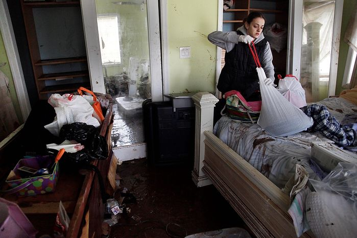 Brooke Clarkin tries to salvage some personal items from her mother's home in Staten Island, New York, Thursday, Nov. 1, 2012. Her mother's home was not only flooded to the ceiling, but was swept off its foundation and was carried to the other side of the street. The National Guard and fede