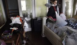 Brooke Clarkin tries to salvage some personal items from her mother's home in Staten Island, New York, Thursday, Nov. 1, 2012. Her mother's home was not only flooded to the ceiling, but was swept off its foundation and was carried to the other side of the street. (AP Photo/Seth Wenig)