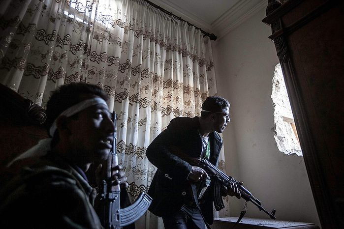 In this Thursday, Nov. 1, 2012 photo, rebel fighters watch over enemy positions as they wait for Syrian army troops to enter a street during clashes in the Karmal Jabl battlefield in Aleppo, Syria. (AP Photo/Narciso Contreras)
