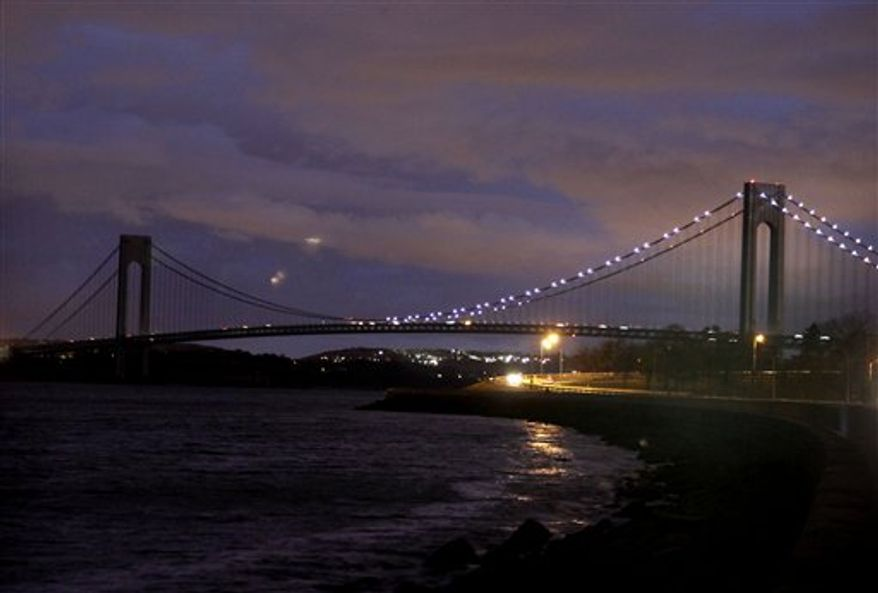 The half of the Verrazano Narrows Bridge attached to Brooklyn is lit while the half attached to Staten Island is dark in New York, Friday, Nov. 2, 2012. The massive storm that started out as Hurricane Sandy slammed into the East Coast and morphed into a huge and problematic system, killing at least 96 people in the United States. Power outages now stand at more than 3.6 million homes and businesses, down from a peak of 8.5 million. The cost of the storm could exceed $18 billion in New York alone. (AP Photo/Seth Wenig)