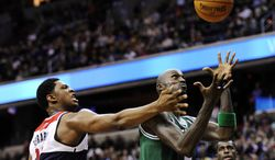 Washington Wizards forward Kevin Seraphin, left, of France, battles for the ball against Boston Celtics forward Kevin Garnett, right, during the second half of an NBA basketball game, Saturday, Nov. 3, 2012, in Washington. The Celtics won 89-86. (AP Photo/Nick Wass)