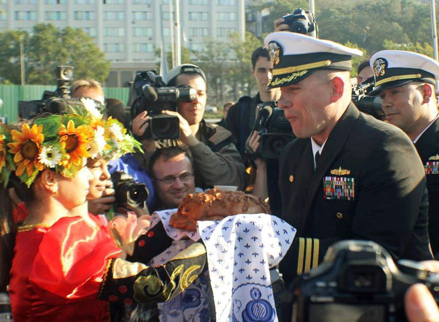 ** FILE ** In this Sept. 20, 2012, photo made available by the U.S. Navy, Cmdr. Joseph R. Darlak, right foreground, commanding officer of the guided missile frigate USS Vandegrift, takes a bite of a traditional offering of bread and salt after arriving in Vladivostok for a port visit during operations in the Western Pacific. Cmdr. Darlak was relieved of command Friday, Nov. 2, 2012, in San Diego, after an investigation for demonstrating poor leadership and failing to ensure proper officer conduct during the three-day September stop. (AP Photo/U.S. Navy Photo by Lt. J.G. Ryan P. Mutha)
