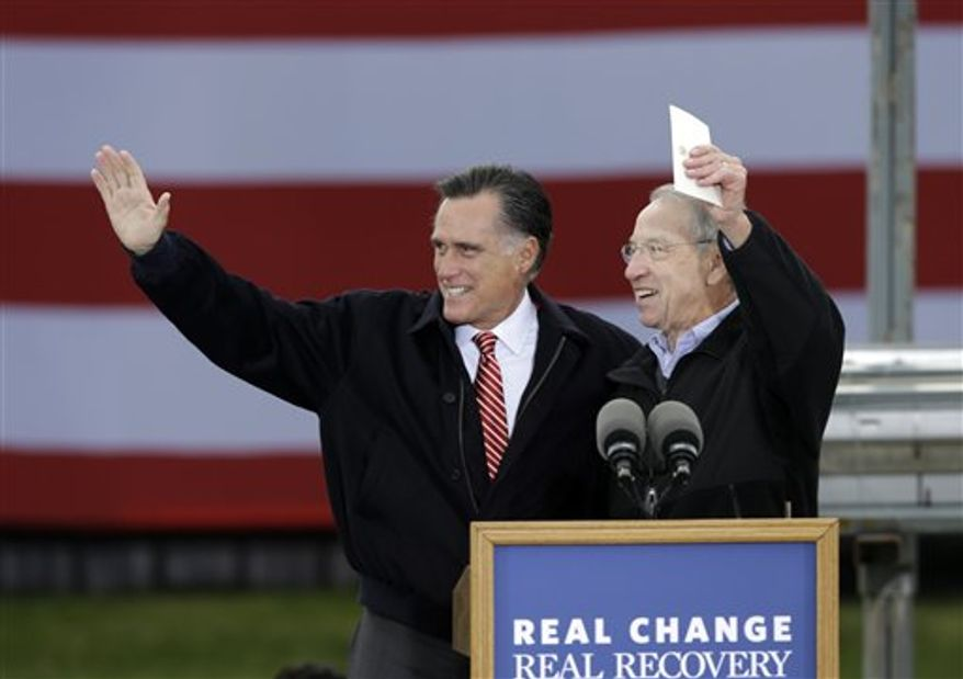 Republican presidential candidate, former Massachusetts Gov. Mitt Romney and Sen. Charles Grassley, R-Iowa, wave before Romney spoke about the economy during a campaign stop at Kinzler Construction Services, Friday, Oct. 26, 2012, in Ames, Iowa. (AP Photo/Charlie Neibergall)