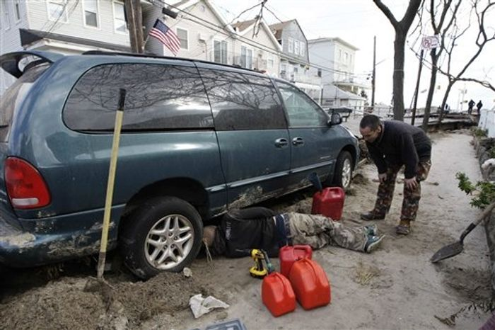 Liam Thomas, right, watches as a friend extracts gasoline from an approving neighbor's vehicle on Saturday, Nov. 3, 2012, in Rockaway section of New York. More New Yorkers awoke Saturday to power being restored for the first time since Superstorm Sandy pummeled the region, but patience wore thin among those in the region who have been without power for most of the week. (AP Photo/Kathy Willens)