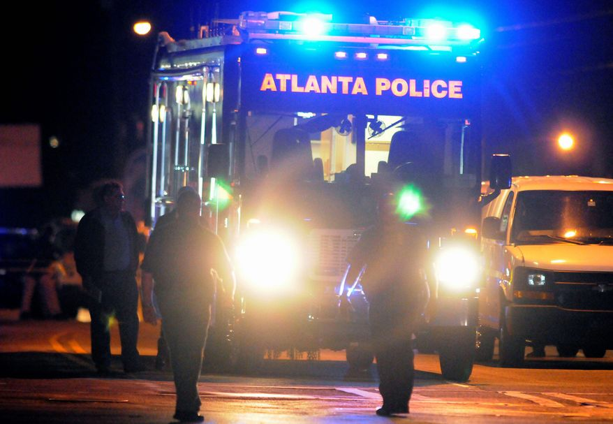 Law enforcement personnel early Sunday examine the scene of an Atlanta Police Department helicopter crash that killed two officers. The subject of their search, a 9-year-old boy who had run away from home, turned up hours later. (Associated Press)