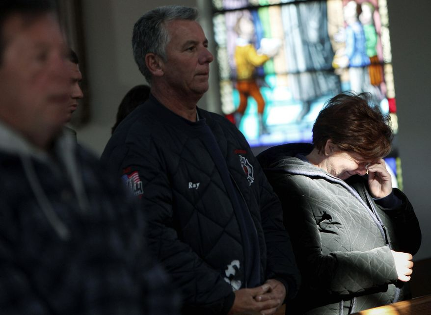 Maryann Eger cries during Mass in the New Dorp neighborhood of Staten Island on Sunday. Churchgoers packed the pews in parkas, scarves and boots and looked for solace in their faith. Hundreds of thousands of New Yorkers are faced with no electrical service. (Associated Press)