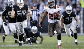 Tampa Bay Buccaneers running back Doug Martin (22) runs for a 67-yard touchdown against the Oakland Raiders during the third quarter of an NFL football game in Oakland, Calif., Sunday, Nov. 4, 2012. Martin, a rookie who was born in Oakland, rushed for a franchise-record 251 yards and four touchdowns. (AP Photo/Marcio Jose Sanchez)