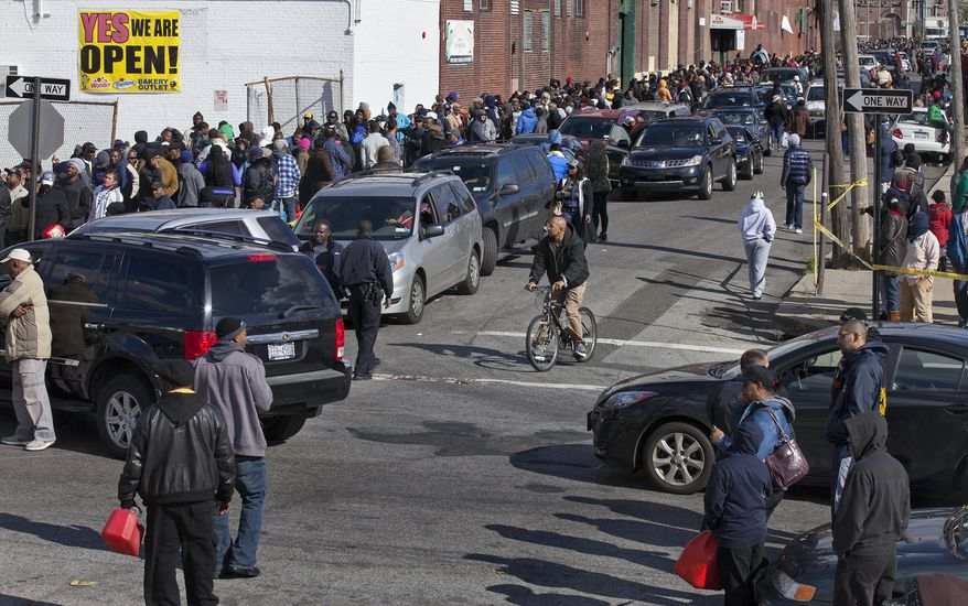 People in cars and on foot line up for free gas in the Jamaica neighborhood of the Queens borough of New York on Saturday, Nov. 3, 2012, in the wake of superstorm Sandy. (AP Photo/Craig Ruttle)