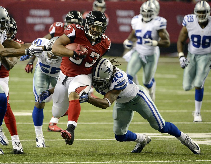 Atlanta Falcons running back Michael Turner (33) tries to get past Dallas Cowboys safety Danny McCray (40) during the second half of an NFL football game, Sunday, Nov. 4, 2012, in Atlanta. (AP Photo/Rich Addicks)