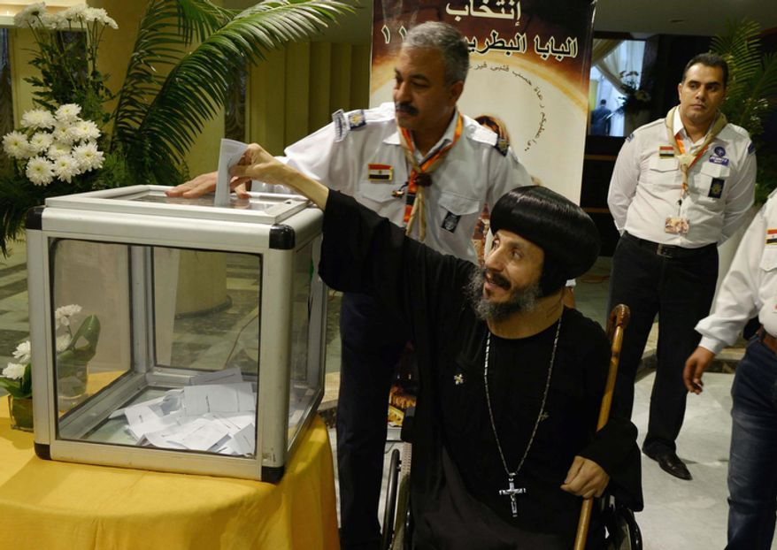 In this Monday, Oct. 29, 2012 file photo, a Coptic clergymen, center, casts his ballot for the new Coptic Pope in elections at the main Coptic cathedral in Cairo, Egypt. (AP Photo/Sami Wahib, file)