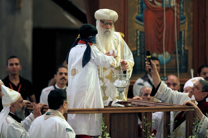 A blindfolded boy draws the name of the next patriarch from a crystal chalice next to acting Coptic Pope Pachomios, center, during the papal election ceremony at the Coptic Cathedral in Cairo, Egypt, Sunday, Nov. 4, 2012.   (AP Photo/Nasser Nasser)