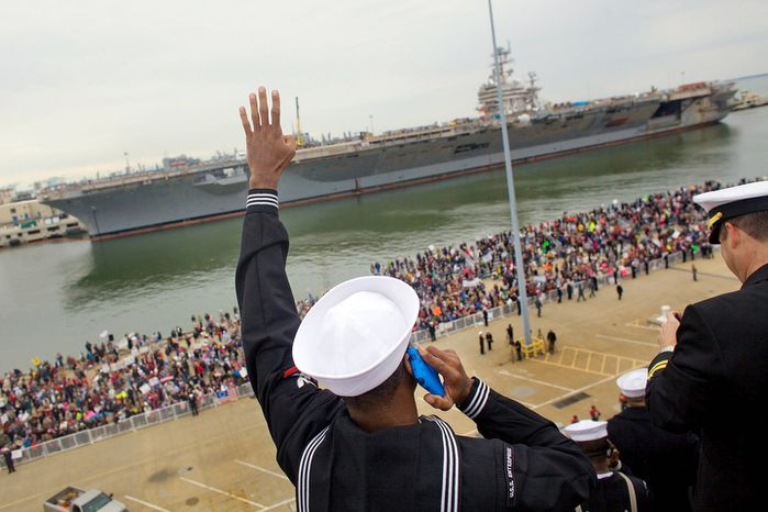Petty Officer 3rd class, Joseph Mustafa, left, waves his family members on the deck of USS Enterprise as it docks at the Pier 12 next to USS Abraham Lincoln during its final homecoming. The Enterprise, the world's first nuclear-powered aircraft carrier ended its remarkable career at sea on Sunday when it pulled into its home port for the final time after participating in every major conflict since the Cuban Missile Crisis of 1962. (AP Photo/The Virginian-Pilot, Hyunsoo Leo Kim)