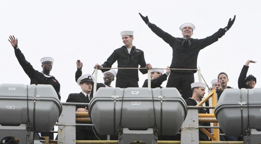 Sailors on board react as the USS  Enterprise returns to Norfolk Naval Station as the 51-year-old ship completes its 25th and final deployment. The Enterprise began shutting down its eight nuclear reactors almost as soon as it arrived at its pier, where thousands of cheering family members and friends welcomed the ship home from its 25th and final deployment after nearly eight months at sea. (AP Photo/The Virginian-Pilot, Steve Earley)