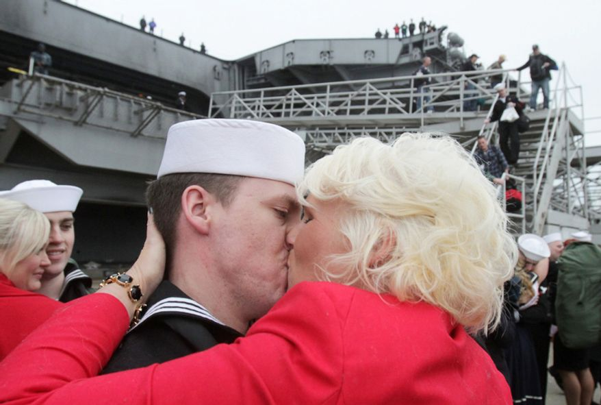 Gina Shelton kisses her husband Petty Officer 2nd class Matthew Shelton as the Enterprise, the world's first nuclear-powered aircraft carrier, returns to Norfolk Naval Station in Norfolk, Va., on Sunday, Nov. 5, 2012.  (AP Photo/The Virginian-Pilot, Steve Earley)