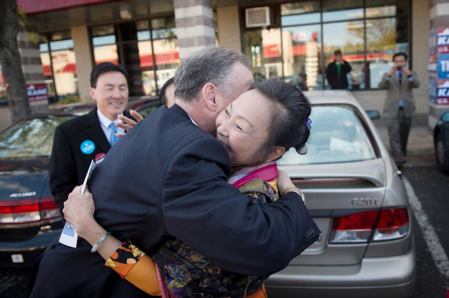Democratic U.S. Senate candidate and former Virginia Governor Tim Kaine hugs friend and campaign volunteer Kim-Ha Ly, of Woodbridge, Va., as he arrives for a rally at the Eden Center in Falls Church, Va. (Rod Lamkey Jr./The Washington Times)